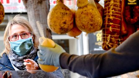 Разпространението на Covid-19 затруднява и търговията, и производството, и туризма: Клиентка със защитна маска се опитва да пазарува, Неапол - 11 март 2020 г.