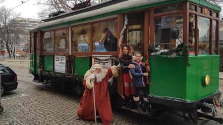 """Водещата на предаването """"Нашият ден"""" Ива Дойчинова с Дядо Коледа до ретротрамвая, като част от кампанията на програма """"Христо Ботев"""" на БНР """"Доброто пътува с трамвая""""."""