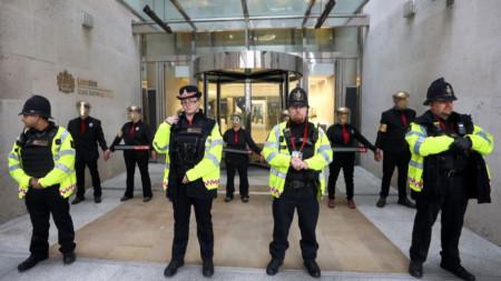 Протестиращи блокираха входа на Лондонската стокова борса като част от тях се залепиха един за друг и към стените.