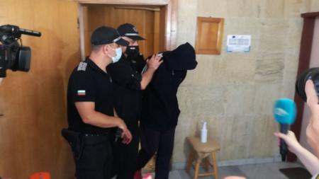 Полицаи водят Крум Йорданов в окръжния съд в Кюстендил на заседание за мярката му за неотклонение.