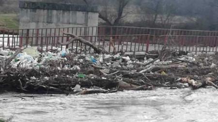 Камари с боклуци, дървета и клони при повредения мост между селата Чeтирци и Ямен.