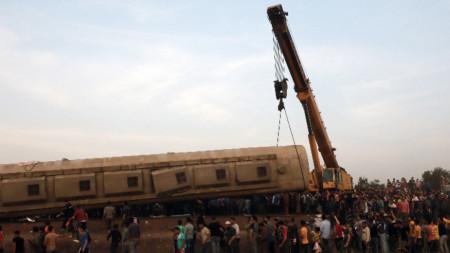 Кран повдига вагон на пътническия влак, дерайлирал в Тух, северно от Кайро, 18 април 2021 г. Според местното министерство на здравеопазването 97 души са ранени, след като няколко вагона излизат от релсите.