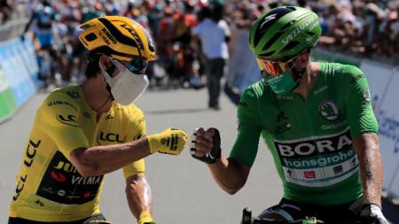 Словенецът Примож Роглич (вляво) облече жълтата фланелка преди началото на етапа.