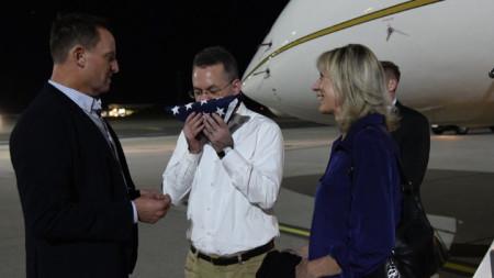 Андрю Брънсън целува знамето на САЩ на летището във ВВС базата Рамщайн, Германия, където бе посрещнат от US посланика в Берлин Ричард Гренел (вляво)