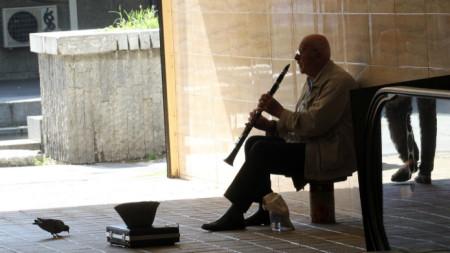 Уличен музикант изкарва прехраната си, свирейки на кларинет