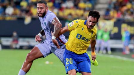 Защитникът на Кадис Иза Карселен (вдясно) пази топката от нападателя на Барселона Мемфис Депай