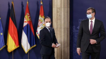 Хайко Маас (вляво) и Александър Вучич пристигат за пресконференцията си в Белград.