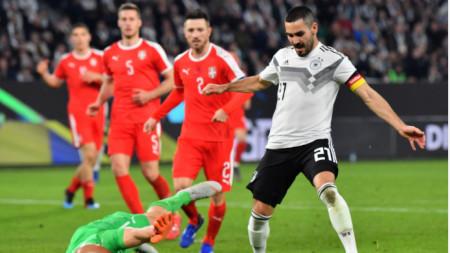Гюндоган се опитва да преодолее сръбския вратар Дмитрович.