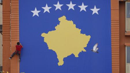 Работник поставя знамето на Косово в центъра на Прищина за 20-ата годишнина от края на войната и влизане на войски на НАТО в провинцията.