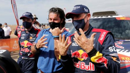 Стефан Петерханзел и директорът на Рали Дакар Давид Кастера показват заедно колко титил има французинът в състезанието.