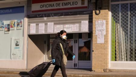 Жена минава пред офис за регистриране на безработни в Мадрид. През март са подадени 302 хил. молби за обезщетения.