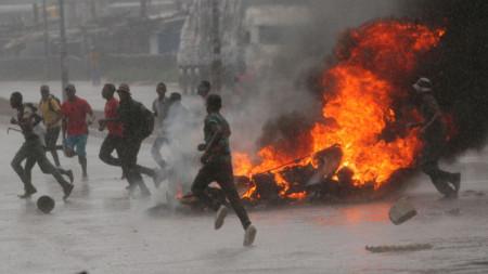 Хора бягат на фона на подпалена барикада в Хараре при дъжд на протест срещу поскъпване на горивата през януари.
