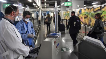Заради случаите на коронавирус в Италия правителството на Северна Македония засили граничния контрол. На снимката: Медицински персонал проверява пътниците на летището в Скопие.