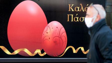 Мъж с маска преминава край надпис с пожелания за добро изкарване на Великденските празници в Атина.