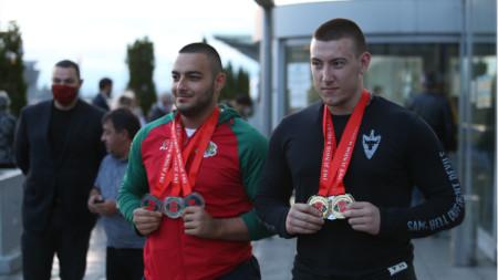 Христо Христов (вдясно) и Васил Маринов позират с медалите си на летище