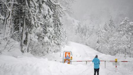 Мъж снима затворен път със знак, предупреждаващ за опасност от лавини край Унтертаурен в австрийската провинция Залцбург.