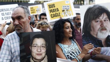 """Журналисти протестират със снимки на задържания журналист и двамата интелектуалци след ареста им през 2016 г. Турски съд днес ги оправда по отправените обвинения в """"терористична пропаганда""""."""