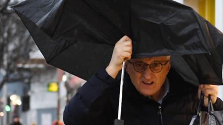Жител на Лондон се опитва да се предпази от дъжда