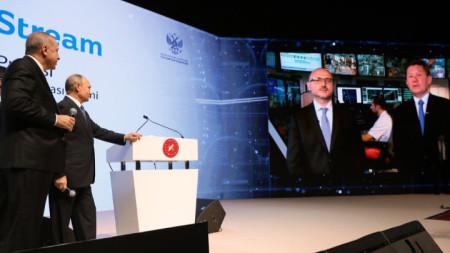 """Реджеп Ердоган (вляво) и Владимир Путин (до него) гледат на екран, показващ шефа на """"Газпром"""" Алексей Милер (вдясно) да говори чрез видеовръзка от кораба Pioneering Spirit на церемонията, отбелязваща завършването на морския участък на газопровода """"Турски поток""""."""