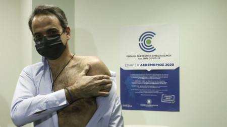 """Гръцкият премиер Кириакос Мицотакис държи ръката си, след като получи втора доза от ваксината на  """"Пфайзер"""" и """"Бионтех"""" в Атина."""