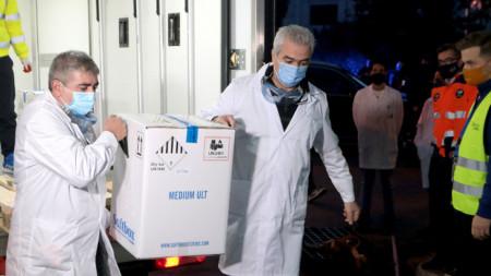 Здравни работници получават първата партида от ваксините на Pfizer-BioNTech срещу Сovid-19 в Атина. Първите дози пристигнаха в Гърция с хладилни камиони през Промахон, граничният пункт с България, в нощта на Бъдни вечер.