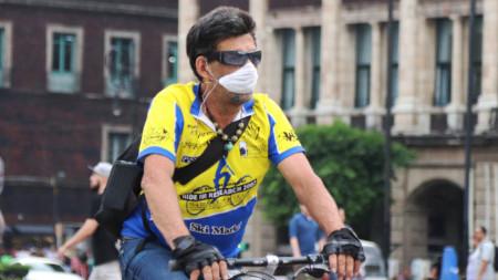 Жител на мексиканската столица със защитна маска се придвижва с велосипед - Мексико Сити, 14 март 2020 г.