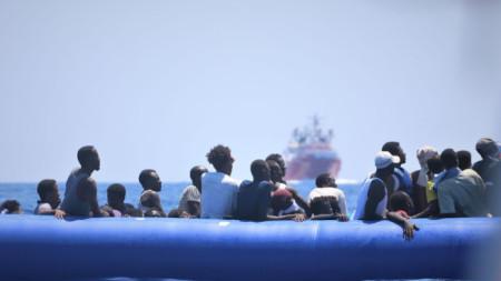 """Мигранти край бреговете на Либия чакат да бъдат спасени от норвежкия кораб """"Оушън Вайкинг""""."""