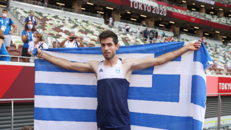Милтиадис Тентоглу позира с гръцкия флаг след победата.