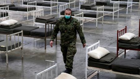 Сръбски военен минава между леглата в още празната полева болница, устроена в залите на Белградския панаир