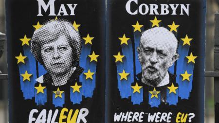 Плакати пред британския парламент в Лондон осмиват премиера Терема Мей и лидера на опозиционните лейбъристи Джереми Корбин.