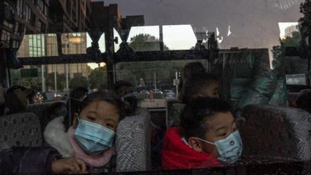 Деца чакат в автобус в Ухан родителите им да ги вземат, след като са били на детска градина, Китай, 31 декември 2020 г.