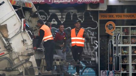 Работници от фирмата за чистота се возят на сметосъбиращия камион