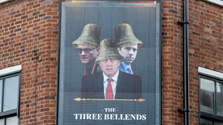 Изображение на министър-председателя на Великобритания Борис Джонсън, здравния министър Мат Ханкок и специалния съветник Доминик Къмингс на табела пред заведение, преименувано на The Three Bellends (Трите разклонения) в знак на протест срещу правителственото отношение към пандемията от коронавирус, Ню Брайтън, Уирал, Англия - октомври 2020 г.