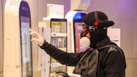 Мъж в защитно облекло проверява автомат за лекарства в супермаркет в град Ухан, провинция Хубей, където за първи път бе регистриран новия корона вирус.