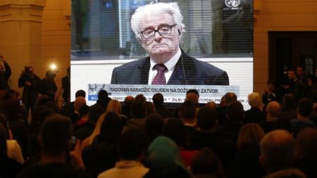 Хора в Сараево гледат репортаж за произнасянето на присъдата срещу Радован Караджич.