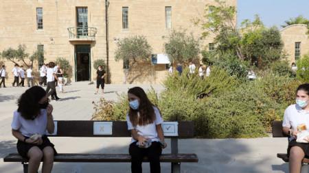 Деца седят с маски на разстояние едни от други на пейка в училищен двор в Никозия - 7 септември 2021 г.