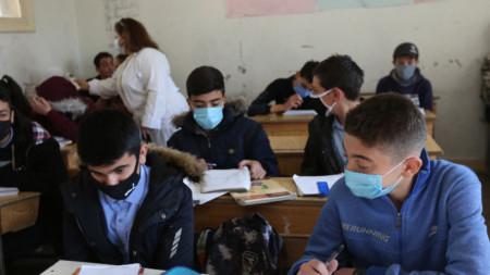Ученици в училище в Дамаск, медицинска сестра измерва температурата им във връзка с пандемията от коронавирус - 29 март 2021 г.