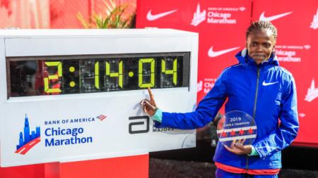 Косгеи позира пред таблото със световния си рекорд в маратона, постигнат в Чикаго.