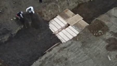 Кадър от видео, заснето от дрон над остров Харт, показва ковчези в масов гроб.
