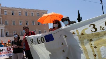 Протестиращите държат банер, изобразяващ евробанкнота по време на протеста в Атина, 16 юни 2021 г.
