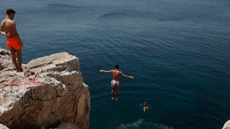 Мъже търсят разхлада от горещините в морето край Атина, 29 юли 2021 г.