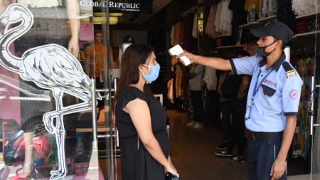 Проверка на температурата преди влизане в магазина в Делхи, 11 юни 2020 г.
