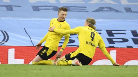 Ройс (вляво) приема поздравления от Холанд за гола си в Манчестър.