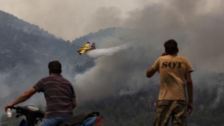 Испански самолет за борба с пожарите хвърля вода върху огнената стихия край село в провинция Мугла.