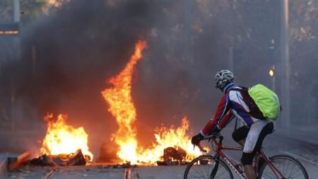 Велосипедист минава край подпален боклук до гимназия в Монпелие.