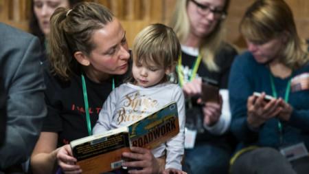 Доун Джоли, която е против задължителното ваксиниране, чете книжка на дъщеря си на изслушването в сенатска комисия за ползите от ваксините.