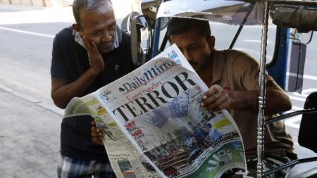 Жители на Коломбо четат вестник, чиято водеща тема са терористичните атаки в страната на католическия Великден.