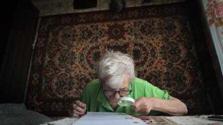 Жена проучва бюлетината при посещение на мобилна изборна секция в дома ѝ в Подолск край Москва.