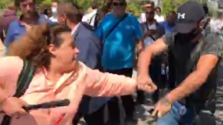 """Младият мъж с маска, шапка и тъмна фланелка първо беше сред хората, провокирали сблъсъци с антиправителствени протестиращи, а след това няколко пъти отне със сила телефона на журналиста от """"Свободна Европа"""" Полина Паунова и го изхвърли."""