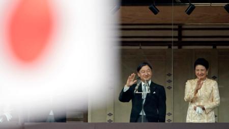 Император Нарухито и императрица Масако отправят приветствие от балкона на двореца.